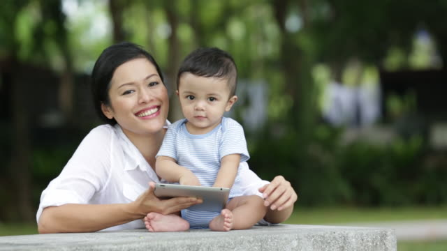 CU Mother and baby playing with a digital tablet outdoors.