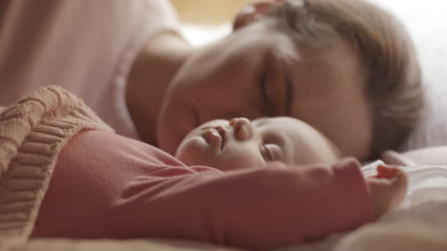 Mother and baby sleeping in bed