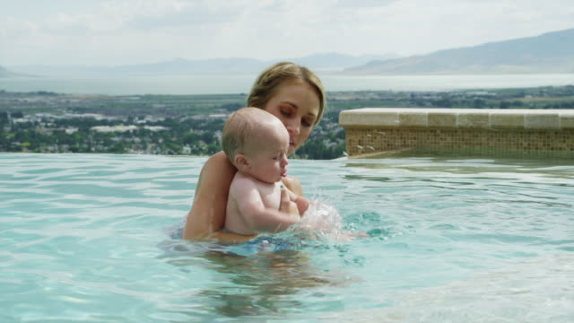 vídeos de stock e filmes b-roll de slo mo ms pan mother and baby son (6-11 months) playing in infinity pool  / cedar hills, utah, usa - 6 11 meses