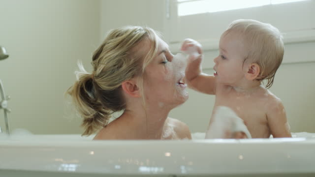 mother and baby taking a bath - vasca da bagno video stock e b–roll
