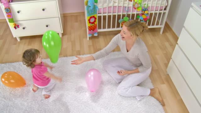 vídeos de stock, filmes e b-roll de grou hd: mãe e bebê fazendo balões - quarto de bebê