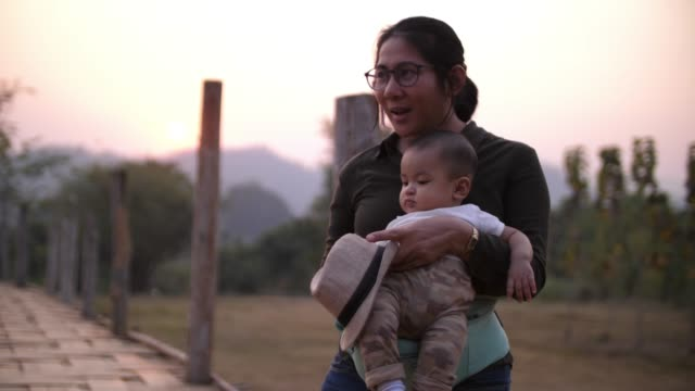 mother and baby walking on the old bamboo bridge in thailand - indigenous culture stock videos & royalty-free footage