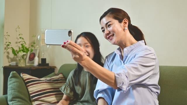 stockvideo's en b-roll-footage met moeder en kind hebben videogesprekken met hun familie met hun smartphone. - zelfportret fotograferen