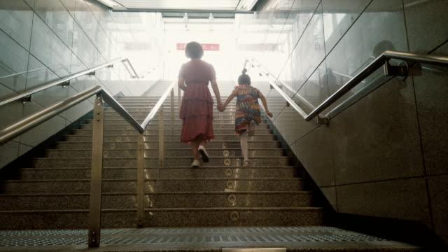 mother and child going together on escalator background - 階段点の映像素材/bロール