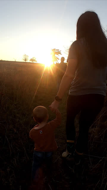 mother and child hold hands while walking during sunset - light beam stock videos & royalty-free footage