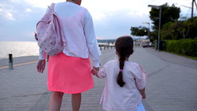 mother and child holding hands walking by the sea - rucksack stock videos & royalty-free footage