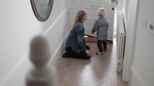 Mother and child kissing goodbye at home