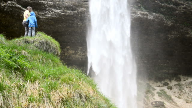mother and child looking at waterfall - unknown gender stock videos & royalty-free footage