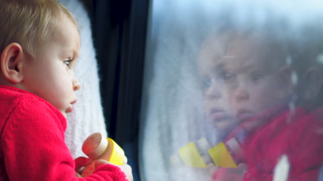mother and child looking through window at the bus - cute stock videos & royalty-free footage