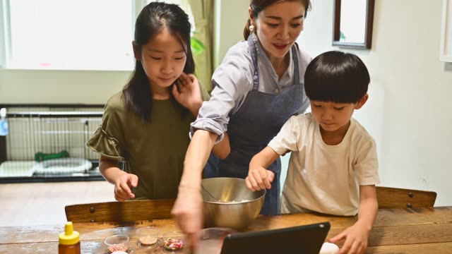 mother and child making pancakes while watching the recipe on the tablet. - family with two children stock videos & royalty-free footage