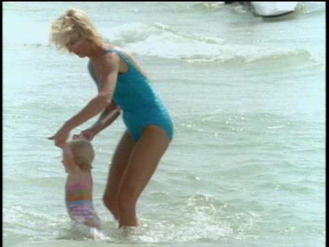 vídeos de stock e filmes b-roll de mother and child playing in water at beach in st petersburg florida - 1980