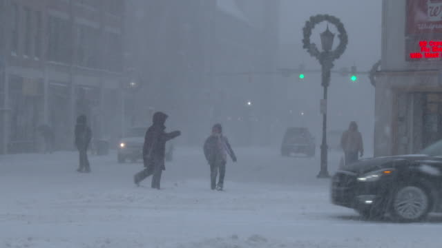 A mother and child struggle to make their way across a busy intersection in Waterbury Connecticut as strong winds and heavy snow create near whiteout...