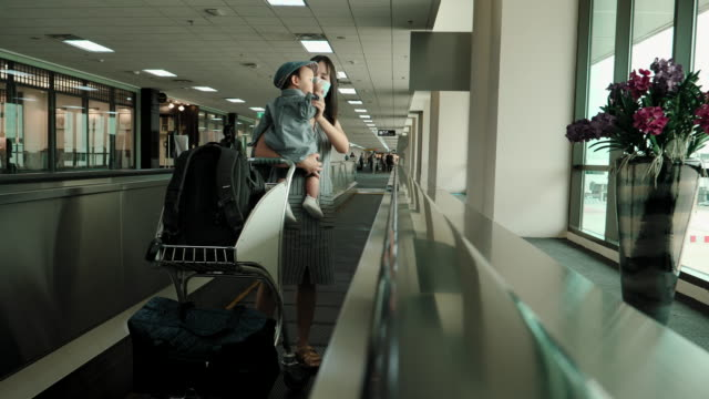 mother and child traveling at the airport - 6 11 months stock videos & royalty-free footage