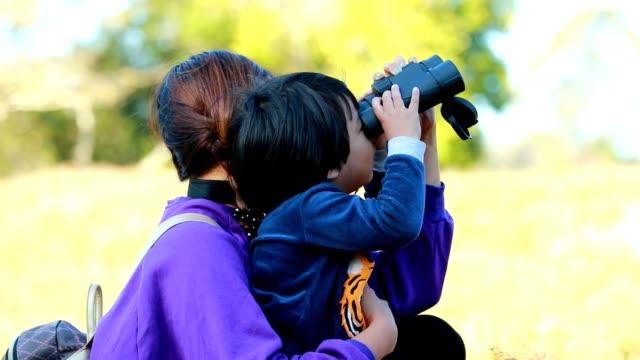 stockvideo's en b-roll-footage met moeder en kind met verrekijkers in het bos, slow motion - verrekijker
