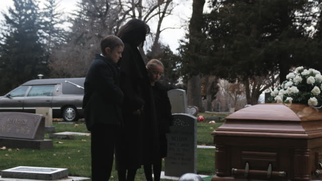 stockvideo's en b-roll-footage met mother and children at a funeral - weduwe
