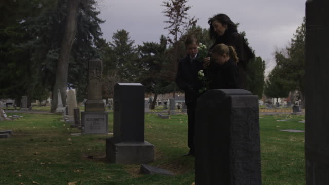mother and children at a gravesite