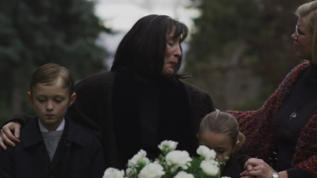 vídeos de stock, filmes e b-roll de mother and children being consoled at a funeral - widow