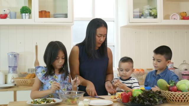 vídeos de stock e filmes b-roll de mother and children cooking salad together - merenda escolar