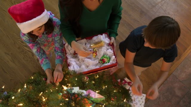 stockvideo's en b-roll-footage met mother and children decorating a christmas tree - kerstboom versieren