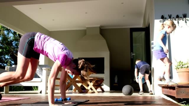 vídeos de stock e filmes b-roll de mother and children doing a home workout together - activity