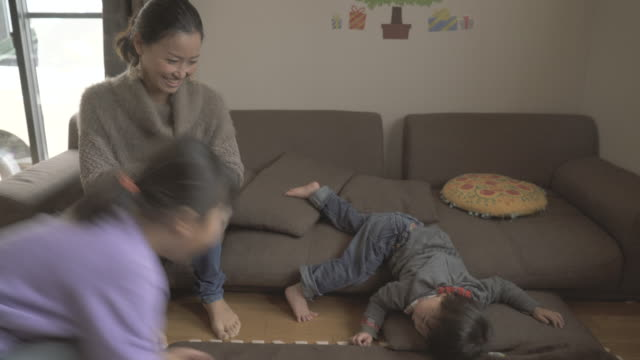 mother and children enjoying in the room - いたずら点の映像素材/bロール