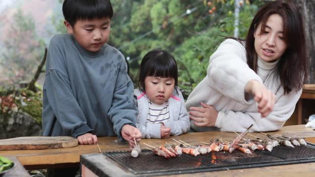 vídeos de stock e filmes b-roll de mother and children grilling shrimps on the grill - atividades ao ar livre