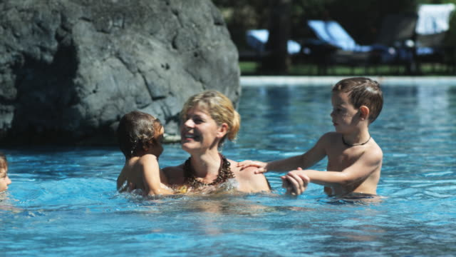 mother and children in a swimming pool - familie mit drei kindern stock-videos und b-roll-filmmaterial