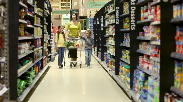 vidéos et rushes de mother and children in supermarket - plan large