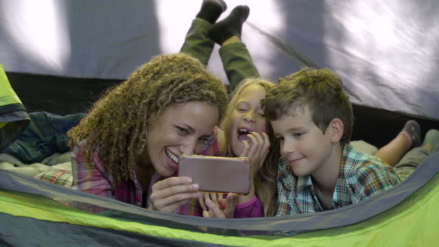 vídeos de stock e filmes b-roll de mother and children in tent taking selfies - insólito