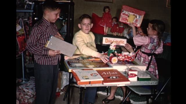 1959 home movie mother and children opening christmas presents and showing gifts / toronto, canada - 1959 stock videos & royalty-free footage