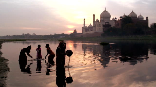 a mother and children play in the water of river yamuna near the taj mahal in agra, india. - taj mahal stock videos and b-roll footage