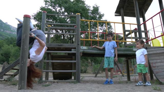 vídeos de stock e filmes b-roll de mother and children playing in the park at playground - equipamento de parque infantil