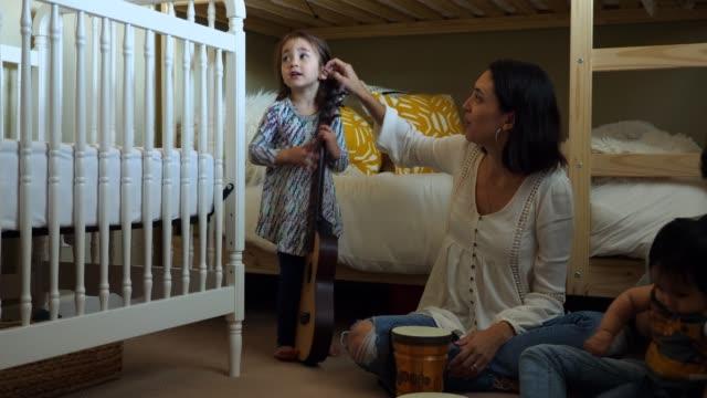 vídeos y material grabado en eventos de stock de ms mother and children playing together on floor of bedroom - cuidado