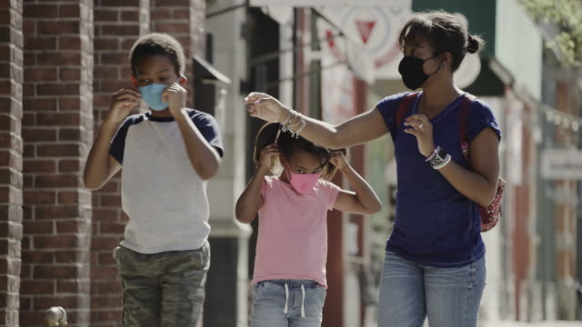 mother and children putting on protective masks before entering building / provo, utah, united states - provo stock-videos und b-roll-filmmaterial