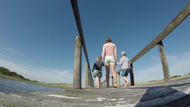 Mother and children walking over a wooden bridge