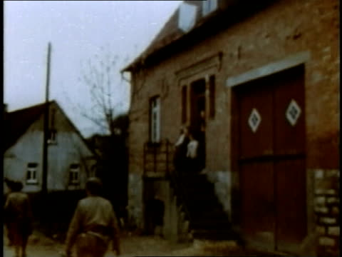 mother and children watch from doorway as american soldiers march into village / germany - 1945 stock-videos und b-roll-filmmaterial