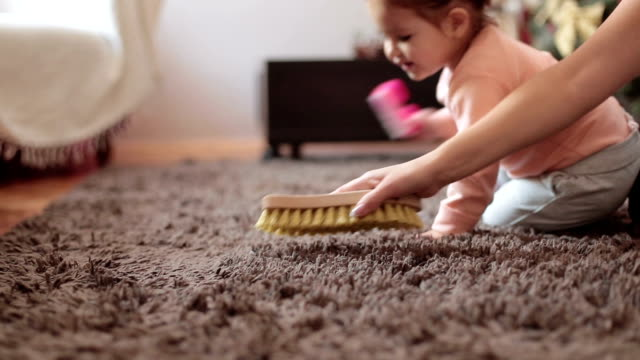 mother and cute baby girl brushing the rug , baby is learning how to clean and assist her mother - chores stock videos & royalty-free footage