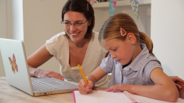 mother and daughter aged 8 years doing homework at kitchen table using laptop - 8 9 years stock videos & royalty-free footage