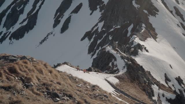 stockvideo's en b-roll-footage met moeder en dochter alpinist ascend rocky trail up mountain - schaal begrippen