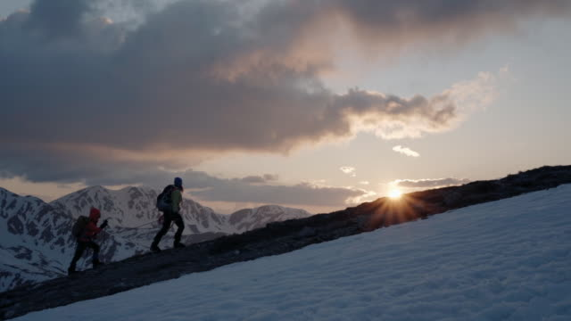 mother and daughter alpinist ascending mountain in winter, sunset lighting - scalare video stock e b–roll