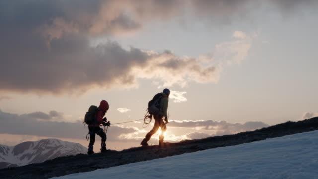 vídeos de stock e filmes b-roll de mother and daughter alpinist ascending mountain in winter, sunset lighting - pico da montanha