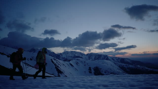 vídeos de stock e filmes b-roll de mother and daughter alpinist ascending mountain in winter, sunset lighting - 10 11 anos