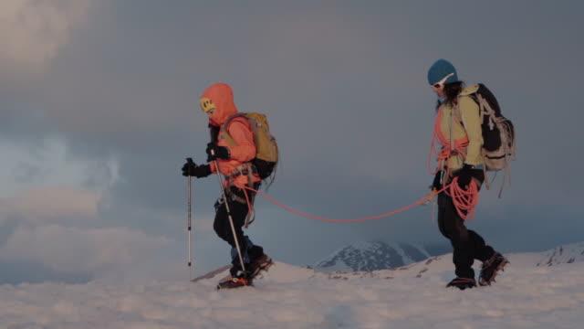 冬の母と娘のアルピニスト上昇山、夕日の照明 - トラッキングショット点の映像素材/bロール
