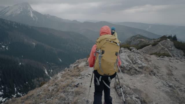 mutter und tochter alpinist machen pause auf felsigen berggipfel, um die aussicht unten zu genießen - kamerafahrt auf schienen stock-videos und b-roll-filmmaterial