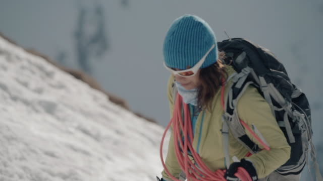mother and daughter alpinists hike up snowy mountain in winter - sunglasses stock videos & royalty-free footage