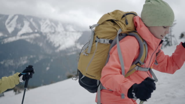 mother and daughter alpinists hike up snowy mountain in winter - 30 seconds or greater stock videos & royalty-free footage