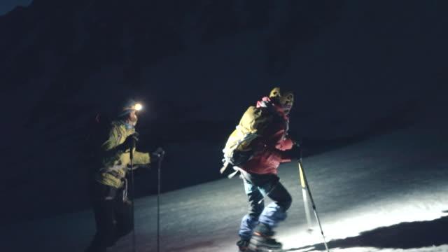 vidéos et rushes de alpinistes de mère et de descendant marchant vers le haut de la crête enneigée de montagne à l'aube - lampe frontale