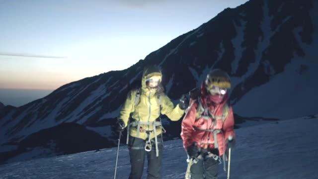 夜明けに雪山の尾根をハイキングする母と娘のアルピニスト - ヘッドライト点の映像素材/bロール