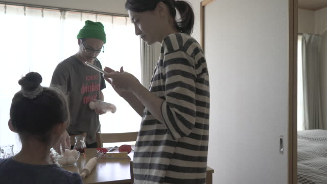 mother and daughter and friends are preparing homemade cookies in room. - two generation family stock videos & royalty-free footage
