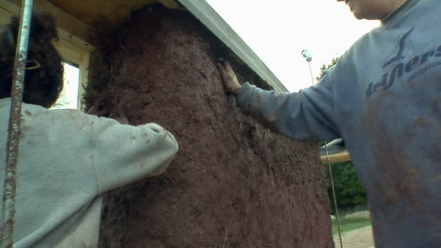 cu pan mother and daughter (4-5) applying adobe mud mixture to the walls of a straw house under construction, grass lake, michigan, usa - straw stock videos & royalty-free footage